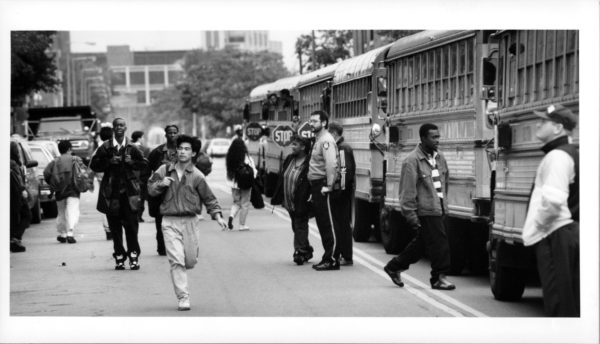 Black and white photo showing police and African American students standing in front of a row of school-buses outside of Charlestown High School