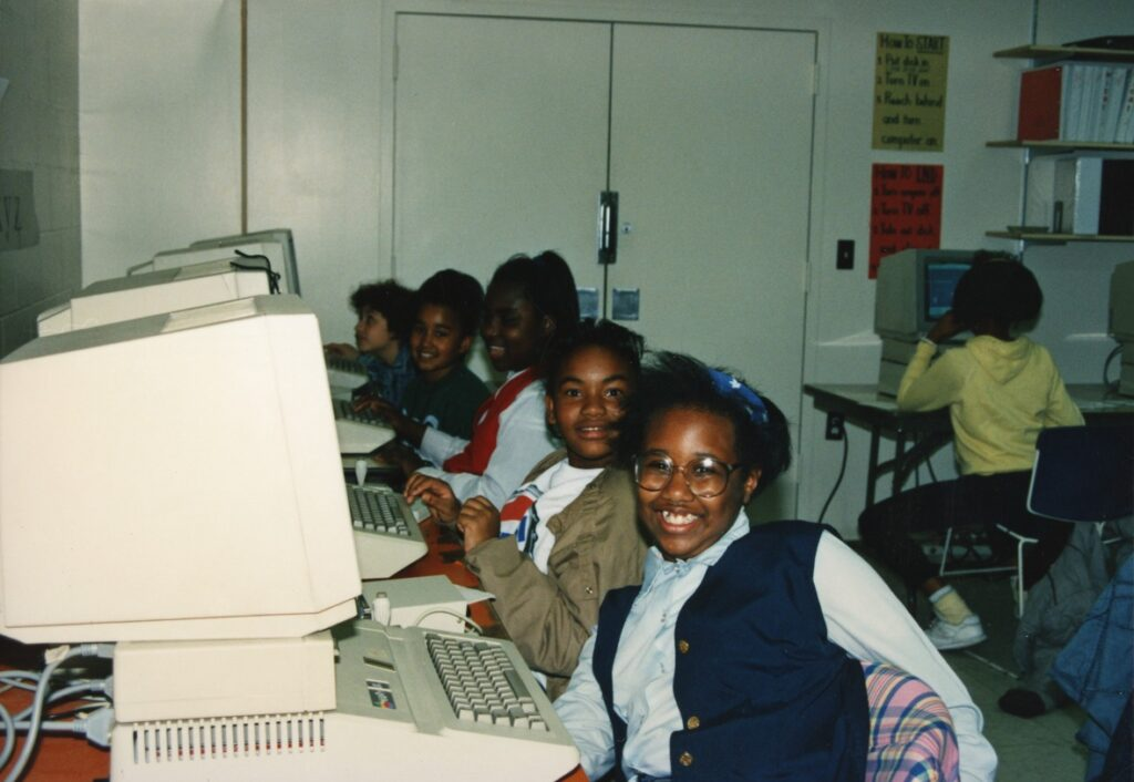 Smiling Black students are in an early computer class, approximately 1980s or early 1990s.